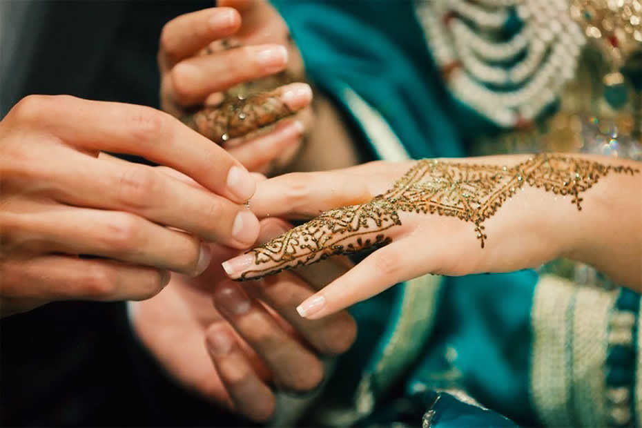 Hand's bride with henna tattos in Morocco during a wedding while husband wear her the ring