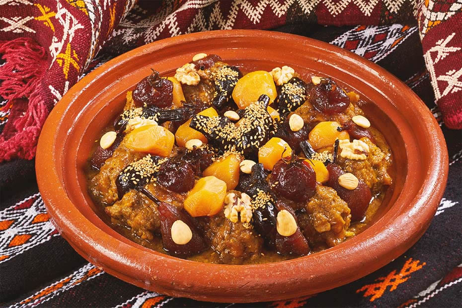 A sweet Moroccan meat tajine with dried fruit and pears decorated with some sesame seeds and grilled almonds