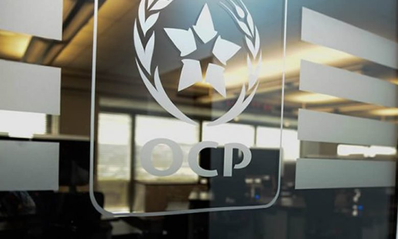 A glass wall with the OCP group's logo