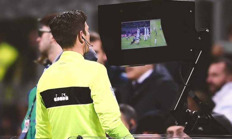 An arbitrator using a Video Assitant Referee (VAR) during a match
