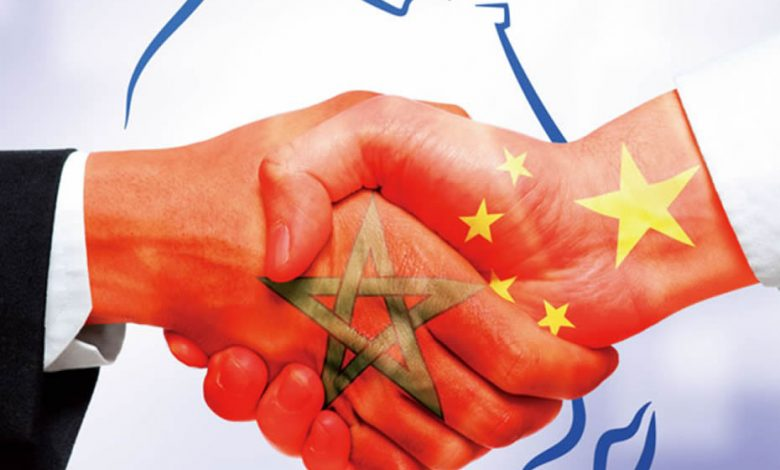 Handshake of two hands, on one is the Moroccan flag and on the other is the Chinese flag.