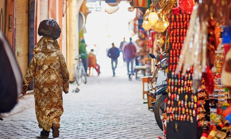 A Moroccan woman in a beautiful stylized djellaba walking in a Moroccan souk