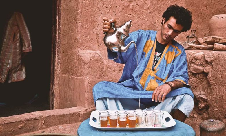 A Moroccan man dressed in a traditional blue Sahrawi clothing with yellow patterns is pouring Moroccan tea from a height