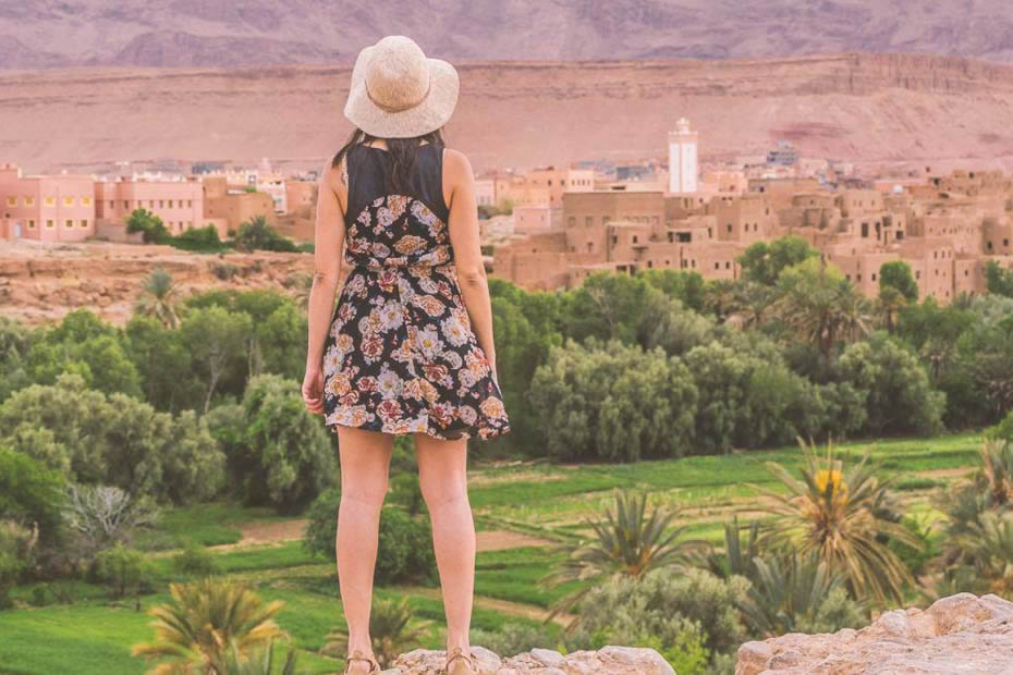 A woman wearing a short dress and a hat looking at the view of Morocco