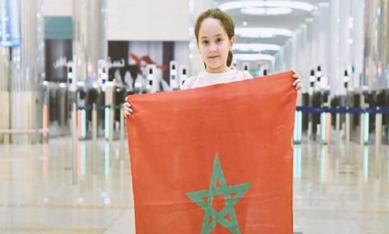 9-year-old Moroccan girl, Meriem Amjoune, winner of the Arab Reading Challenge 2018, holding the Moroccan flag.