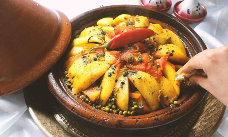 A Moroccan tagine with potatoes, peas, carrots, and tomatoes with a hot pepper on top as decoration.