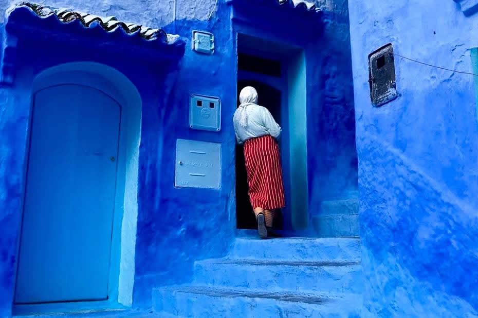 Why is the city of Chefchaouen in Morocco completely blue : a Moroccan woman wearing traditional Moroccan clothes of north of morocco