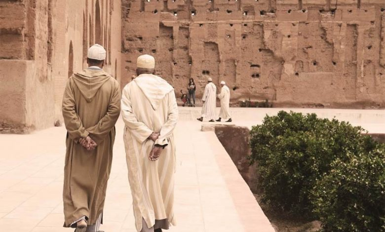A picture from behind of two Moroccan men walking, hands behind their backs, wearing traditonnal Moroccan cloths called djellaba.