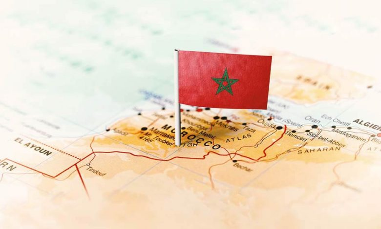 Moroccan flag pointing at Morocco on a world map