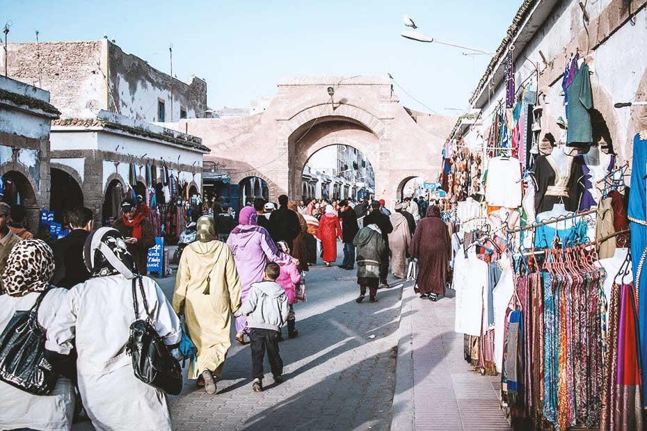 What do locals wear in Morocco: Moroccan locals wandering through a Moroccan souks wearing djellabas.