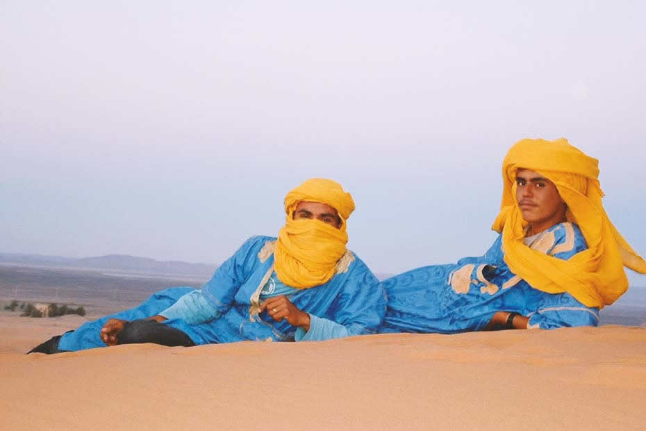 What to wear in the Morocco desert: two men laying on the sand dressed in a traditional blue Sahrawi clothing with yellow patterns and a yellow scarf on their heads.